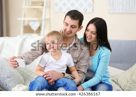 Happy family making selfie with mobile phone on couch, indoor