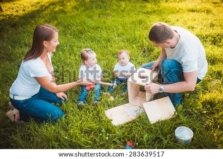 Happy family making Wooden birdhouse in summer green park