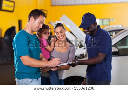 happy family man signing invoice in car repair shop - stock photo