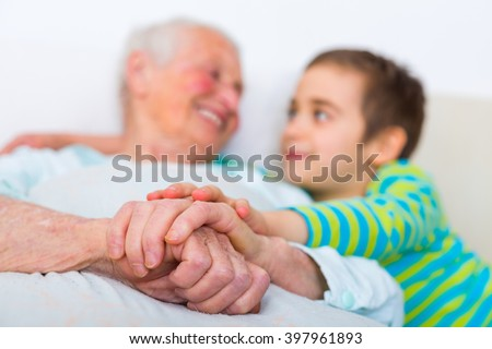Happy family members: grandchild holding grandmother's hands.