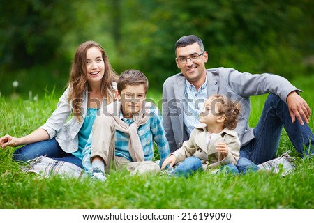 Happy family members looking at camera while sitting in green grass outdoors