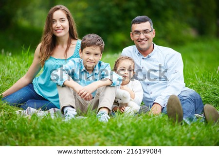 Happy family members looking at camera while sitting on the lawn