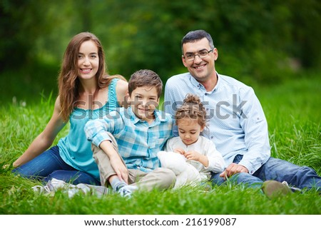 Happy family members relaxing on the lawn in summer