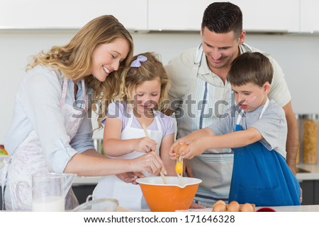 Happy family mixing egg to bake cookies in kitchen - stock photo