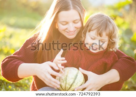 Happy family mom and child outdoors with little pumpkin, copyspace