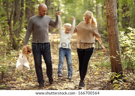 happy family mom dad and daughter walking in the park - stock photo