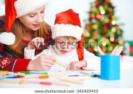 happy family mother and baby child daughter  write a letter to Santa Claus on Christmas Eve