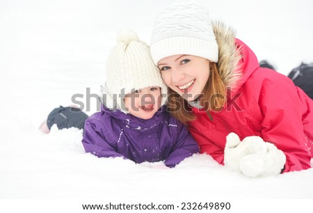 happy family mother and baby girl daughter playing and laughing in winter outdoors in the snow - stock photo