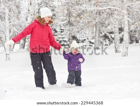 happy family mother and baby girl daughterÃ?Â??run, walk playing  in winter outdoors in the snow - stock photo