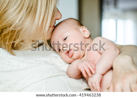happy family mother and baby having fun playing, kissing laughing on the bed - stock photo