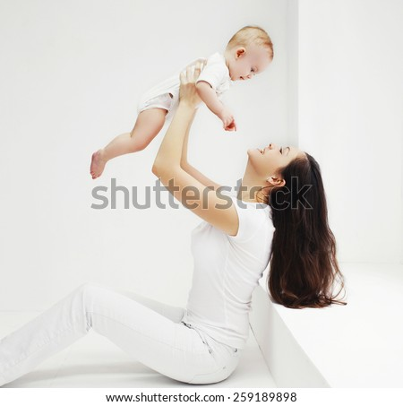 Happy family, mother and baby having fun together at home in white room - stock photo