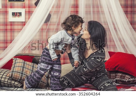 Happy family mother and baby together at home in the cosy atmosphere of the bedrooms in winter interior - stock photo