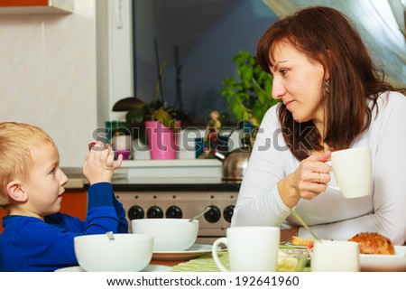 Happy family. Mother and blond son boy kid child eating corn flakes and bread breakfast morning meal together at the table. Home. - stock photo