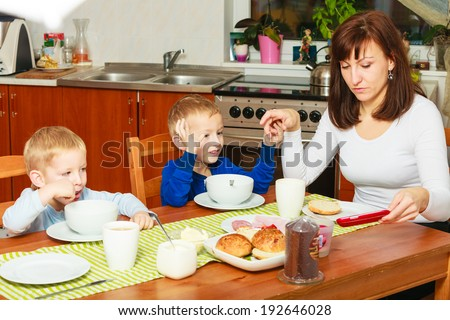 Happy family. Mother and blond sons boys kids children eating corn flakes and bread breakfast morning meal together at the table. Home.