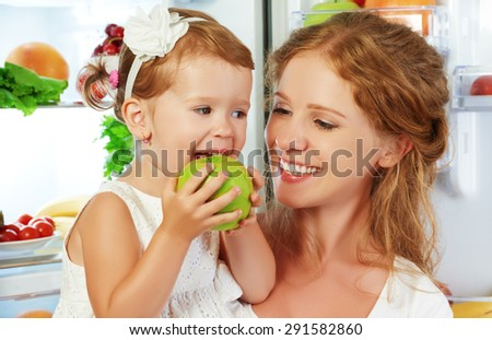 happy family mother and child baby daughter around the refrigerator with healthy food fruits and vegetables - stock photo