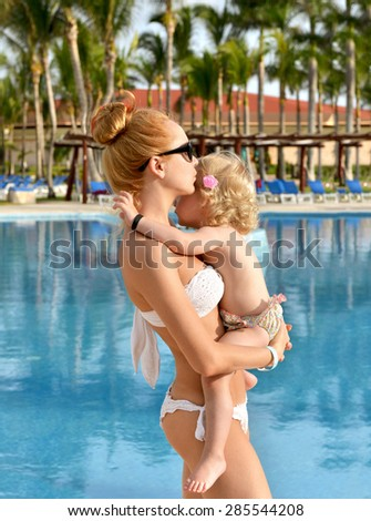 Happy family mother and child baby girl standing near swimming pool hotel tropical beach resort in summer time - stock photo