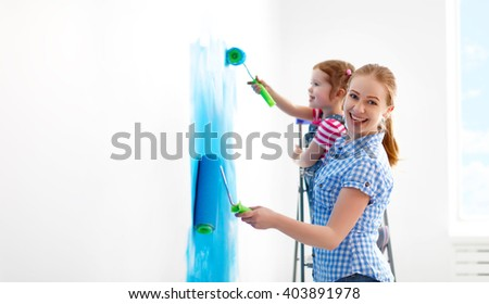 happy family mother and child daughter making repairs, paint the wall at home - stock photo