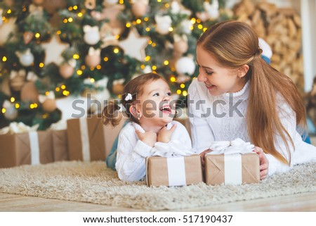 happy family mother and child daughter on Christmas morning at the Christmas tree with gifts