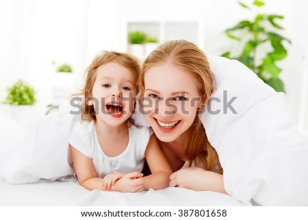 happy family mother and child daughter playing and laughing in bed at home - stock photo