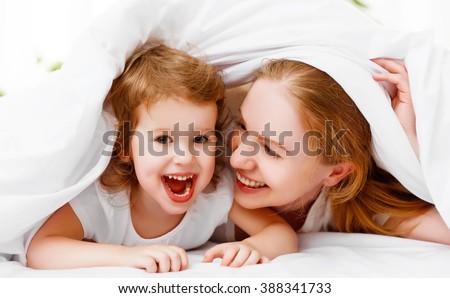 happy family mother and child daughter playing and laughing in bed at home