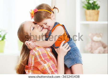 happy family mother and child girl daughter playing  laughing and hugging at home - stock photo
