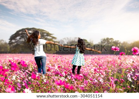 Happy family mother and child girl little daughter playing and running on the meadow - stock photo