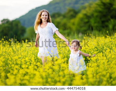 happy family, mother and child girl little daughter playing and running  on the meadow with yellow flowers - stock photo