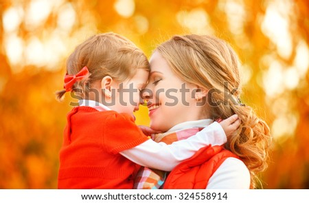 happy family. mother and child little daughter play kissing on autumn walk in nature outdoors - stock photo