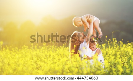happy family, mother and children daughter and baby son on meadow with yellow flowers - stock photo