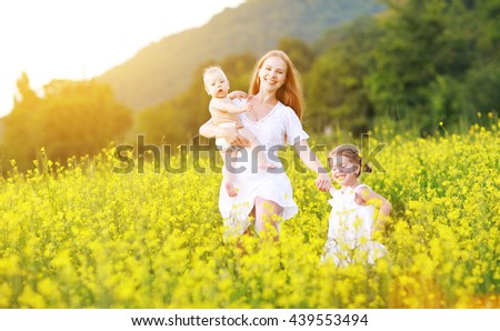 happy family, mother and children girl little daughter and baby running  on meadow with yellow flowers - stock photo
