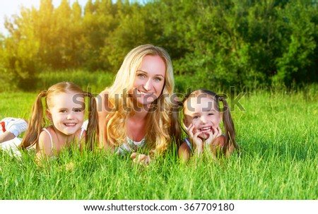 happy family mother and children twin sisters on meadow in the summer on a green grass - stock photo
