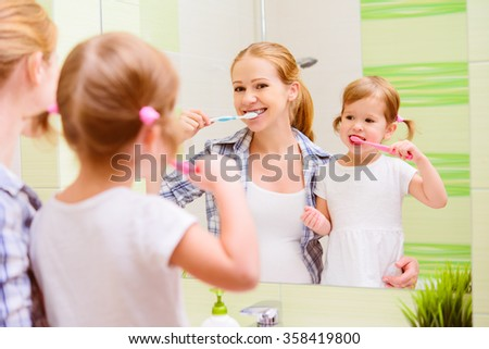 happy family mother and daughter child girl brushing her teeth toothbrushes front of the mirror in the bathroom - stock photo