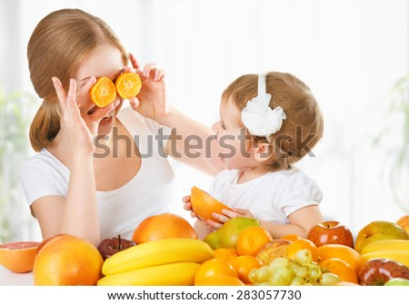 happy family mother and daughter little girl, eat healthy vegetarian food, lots of fruit - stock photo