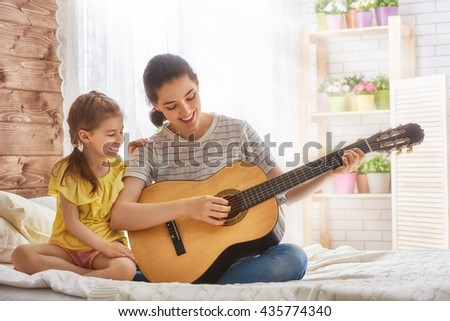 Happy family. Mother and daughter playing guitar together. Adult woman playing guitar for child girl. - stock photo