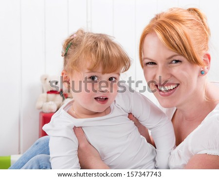 Happy family:  mother and daughter smiling at camera - strawberry blonde hair