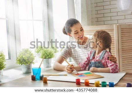 Happy family. Mother and daughter together paint. Adult woman helps the child girl. - stock photo