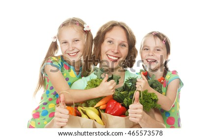 Happy family mother and daughters with bags of vegetables