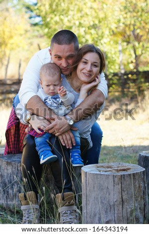 happy family - mother and father is plaing with their baby boy outdoor - stock photo