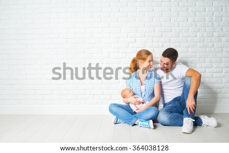 happy family mother and father of a newborn baby sitting on the floor near the blank brick wall - stock photo