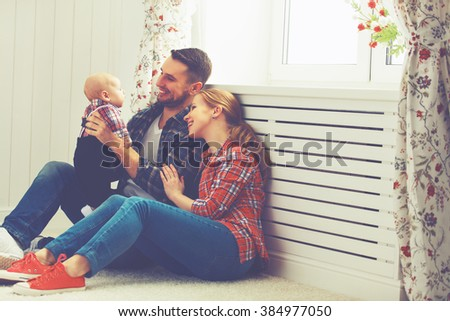 happy family mother and father playing with a baby at home - stock photo