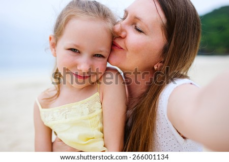 Happy family mother and her adorable little daughter at beach taking selfie - stock photo