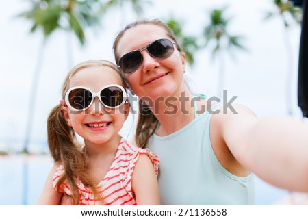 Happy family mother and her adorable little daughter on summer vacation taking selfie with smartphone