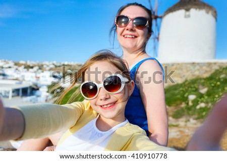 Happy family mother and her adorable little daughter on vacation taking selfie at Little Venice area on Mykonos island, Greece