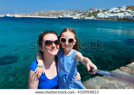 Happy family mother and her adorable little daughter on vacation taking selfie with a stick on Mykonos island, Greece