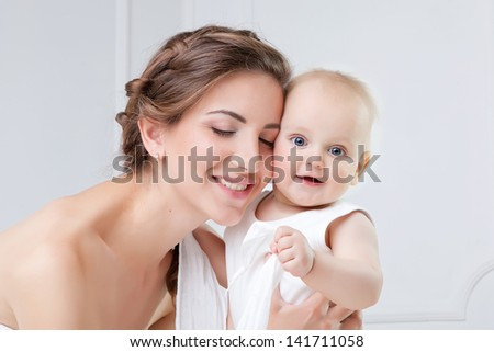 Happy family. Mother and her baby son playing and smiling on bed
