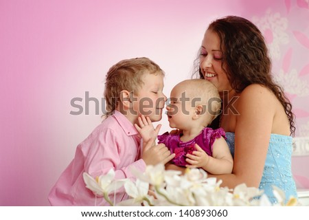 Happy family mother and her children boy and girl sitting indoor and smiling