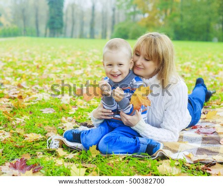 happy family: mother and her son in the autumn park