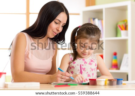Happy family. Mother and kid daughter together paint. Woman helping to child girl.