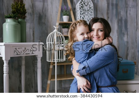 Happy family mother and little daughter hug dressed in denim dress - stock photo