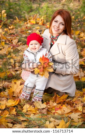 Happy family, mother and little daughter in autumn park